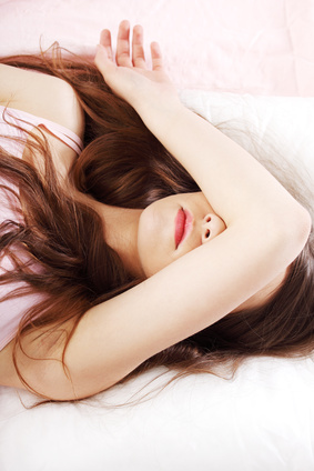 Sad woman is lying in bed with her arm on head and eyes.